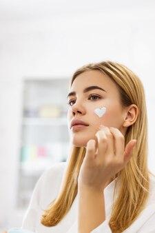 Женщина наносит крем на лицо в форме сердца