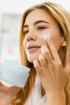 Женщина наносит крем на лицо в форме сердца Premium Фотографии