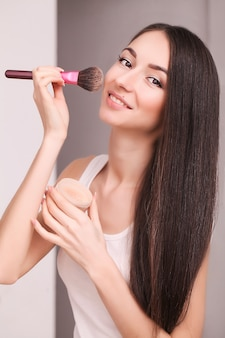 女性はブラシで顔に化粧をします