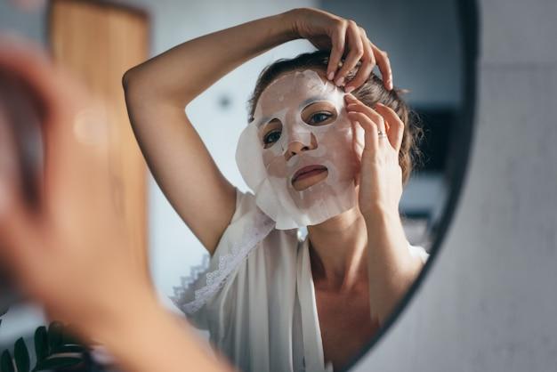 여자는 화장실에서 그녀의 얼굴에 시트 마스크를 적용합니다.