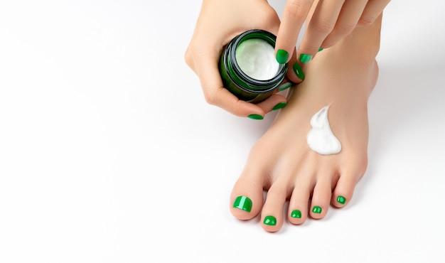 Женщина наносит крем на ноги на белом фоне