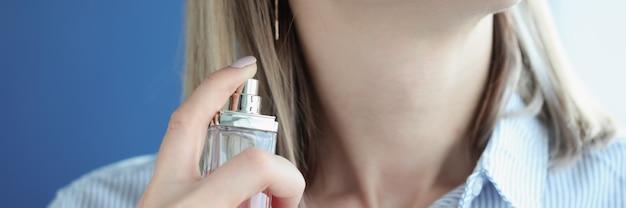 Женщина наносит туалетную воду на шею