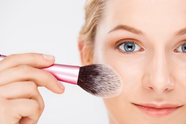 Женщина наносит макияж на лицо кистью