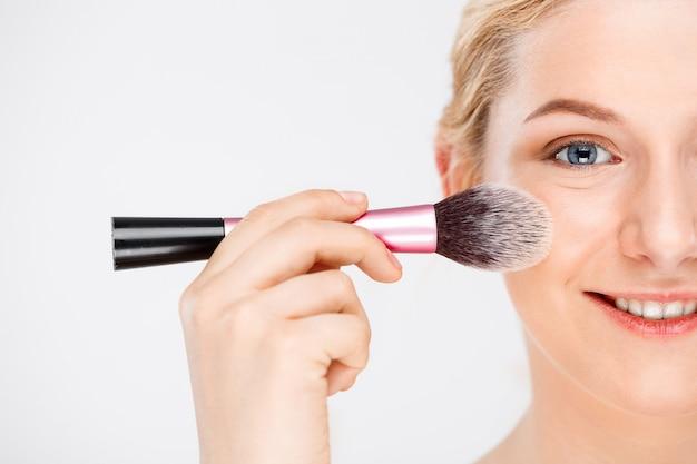 女性はブラシで顔に化粧を適用します