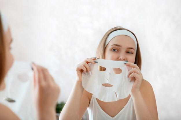 여자는 얼굴에 마스크 시트를 적용합니다. 페이셜 스킨케어 트리트먼트. 10대 소녀는 미용 치료를 받습니다. 홈 뷰티 스파 트리트먼트. 매일의 위생과 회춘. 거울 욕실에서 여성 초상화입니다.