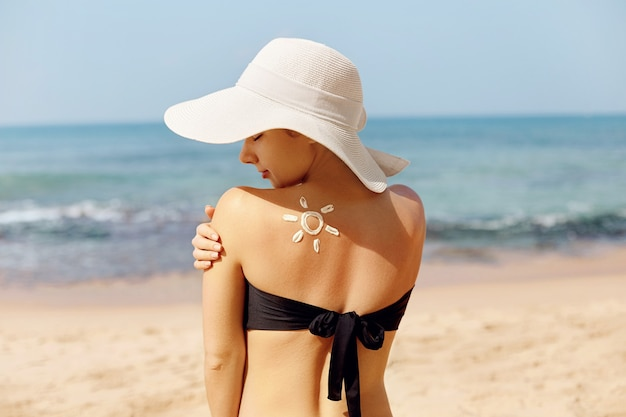 Woman apply sun cream protection cream on her  tanned shoulder.