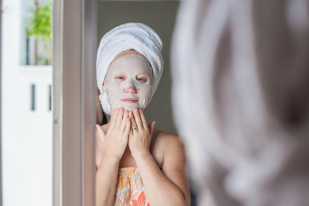 顔のマスクシートを適用する女性