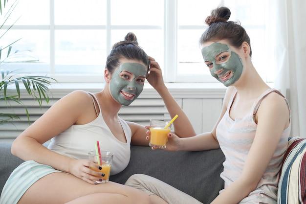 그녀의 친구, 아름다움과 피부 관리 개념에 얼굴 마스크를 적용하는 여자