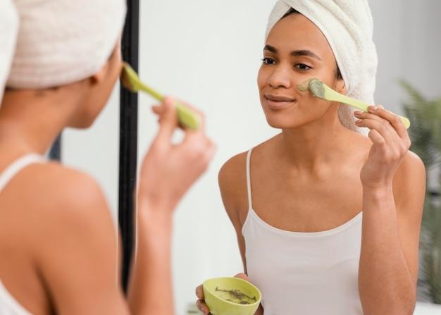 Женщина, наносящая домашнюю маску на лицо