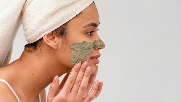 그녀의 얼굴에 수제 치료를 적용하는 여자
