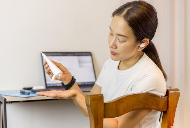 Женщина, применяя алкоголь гель для очистки рук во время работы на ноутбуке дома