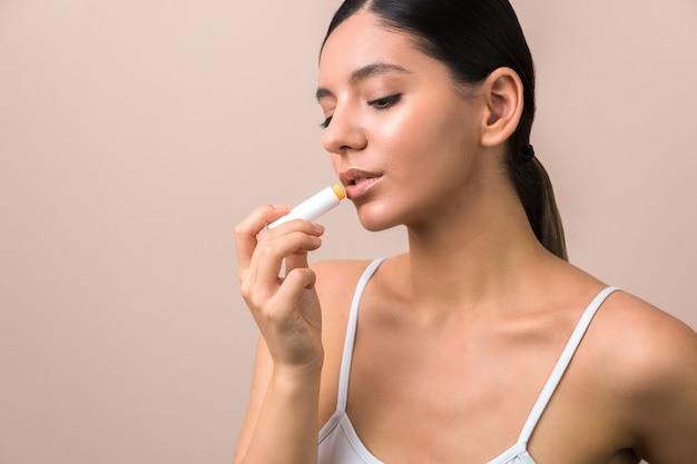 女性の唇に香油を適用します。