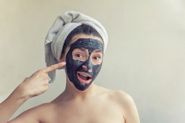 Woman applying black nourishing mask on face