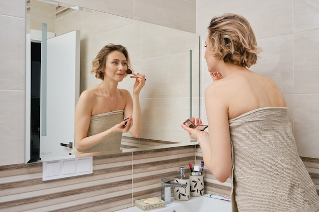 Женщина наносит румяна на лицо, стоя перед зеркалом в ванной комнате