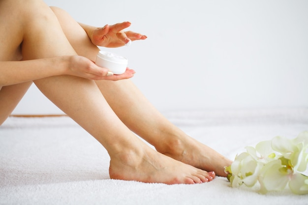 Woman applying body cream on her leg in bedroom