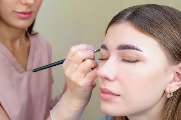 メイクブラシのクローズアップで眉の色合いを適用する女性