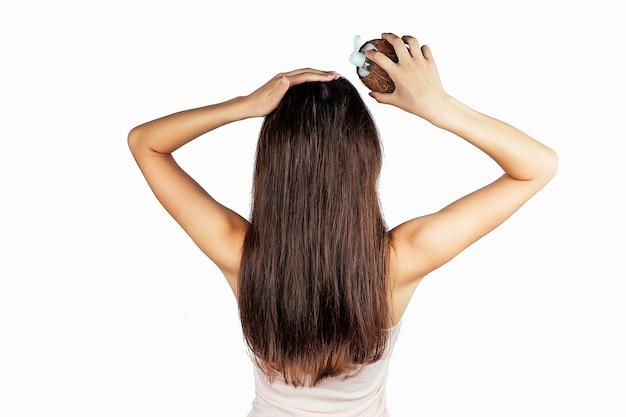 코코넛 오일 병과 모자를 손에 든 머리카락에 흰색 격리된 후면 보기를 적용하는 여자.