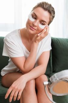 Donna che applica maschera per gli occhi al collagene per idratare