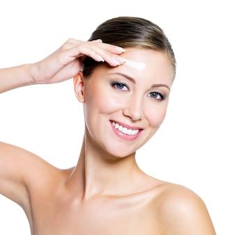 Женщина, применяющая косметический крем
