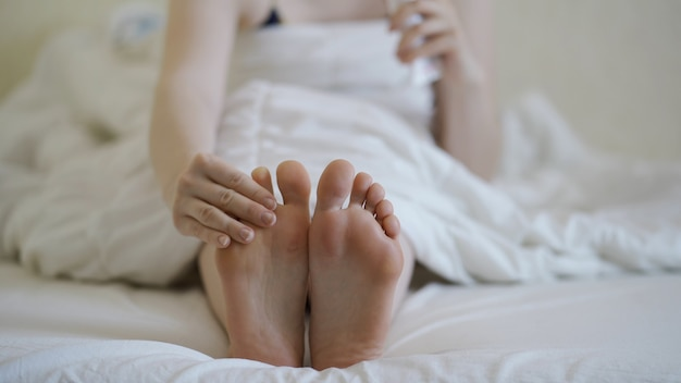 Женщина, применяющая косметический крем для ног, делает массаж ног крупным планом