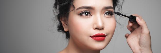 カーリングブラシを使用してまつげに化粧マスカラを適用する女性