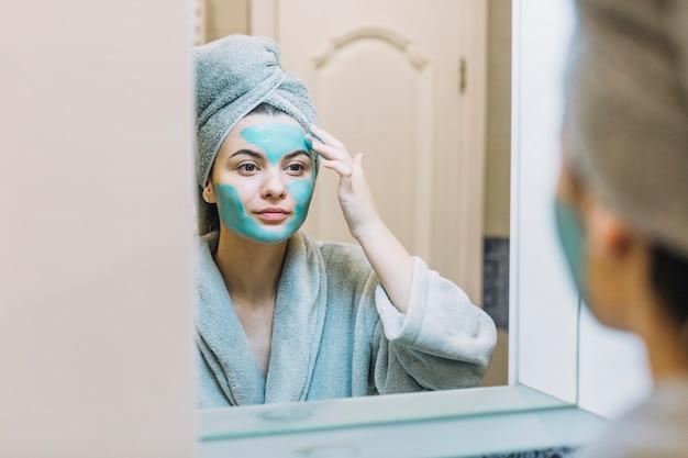 Woman applying cosmetic mask