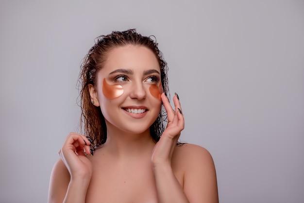 Женщина прикладывая косметические заплаты красных глаз, изолированные на белизне. витаминный помидор с уходом за лицом. маска для лица красоты, уход за кожей и концепция лечения.