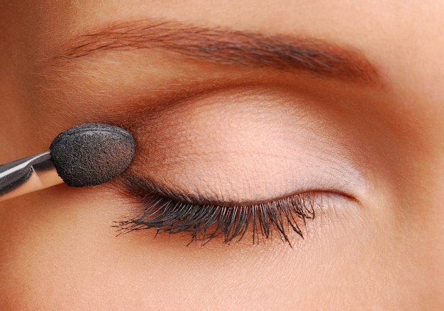 Woman applying cosmetic with applicator on the lid