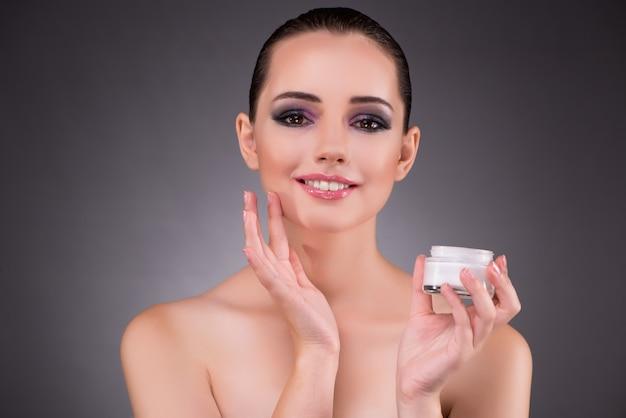 Woman applying cream in beauty