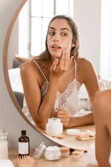 Donna che applica crema e che esamina lo specchio