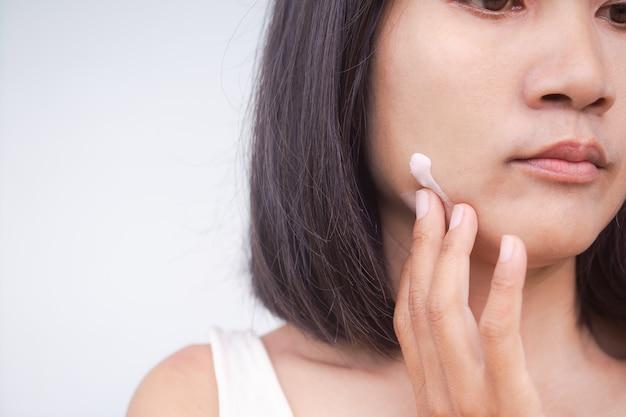 顔にクリーム保湿剤を塗る女性をクローズアップ。本物の肌日焼けアジアタイ。スキンケアと保護のための日焼け止めvua、b。美容コンセプトのコストメティック。