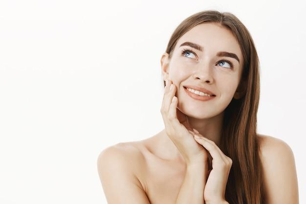 Женщина, наносящая крем на лицо, чувствует кожу мягкой и нежной, стоя мечтательно и в восторге от результата, глядя в верхний левый угол с чувственной улыбкой, касаясь щеки, позирует обнаженной над серой стеной