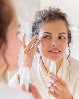 Женщина наносит крем на лицо, глядя в зеркало