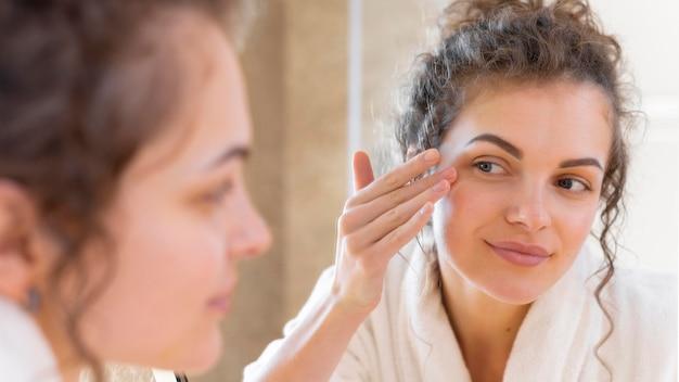 거울을보고있는 동안 얼굴에 크림을 적용하는 여자