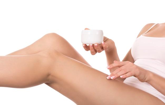 白い壁に彼女の足にクリームを適用する女性。スキンケアと健康の概念。