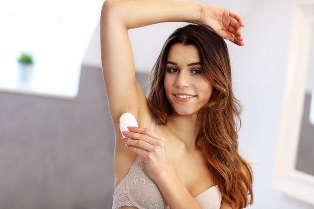 浴室の脇の下にデオドラントを塗る女性