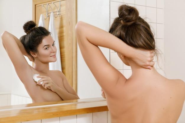 Woman applying deodorant
