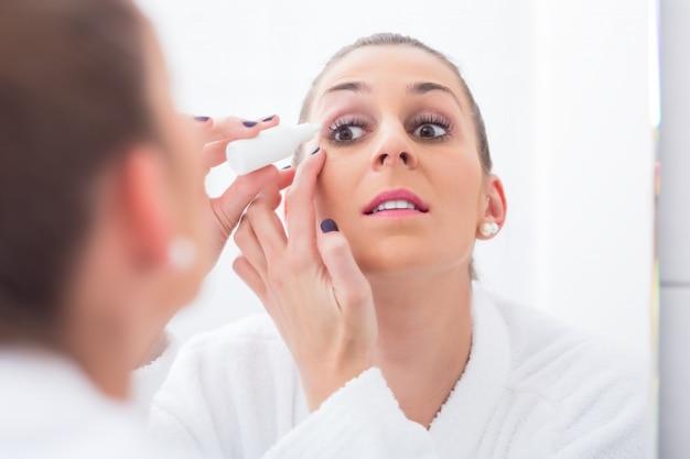 点眼薬を適用する女性
