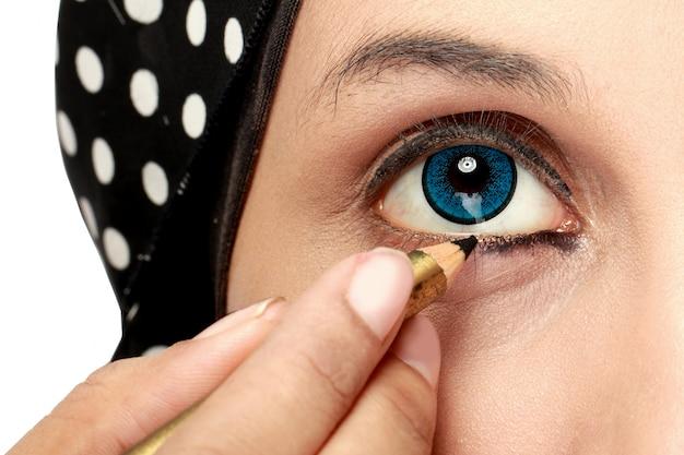 Женщина прикладывая карандаш для глаз