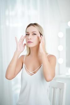目のクリームを適用する女性