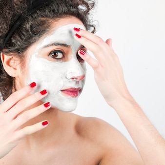 Woman applying face mask on her face against white background