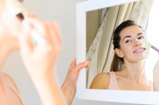 Donna che applica maschera facciale mentre guardarsi allo specchio