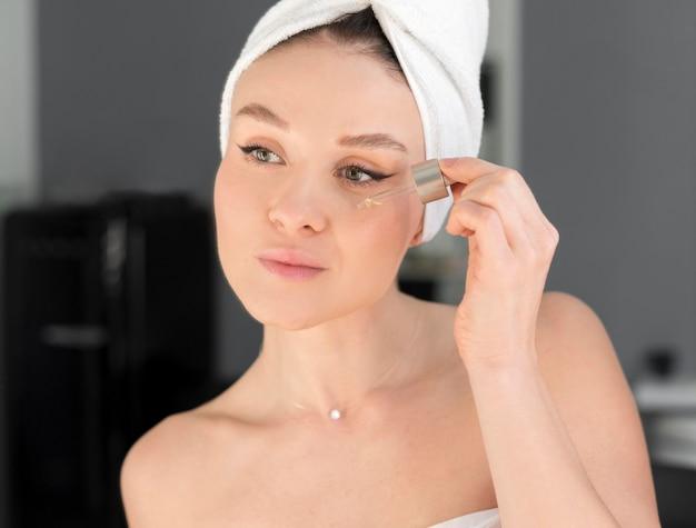 Женщина, применяя сыворотку для лица