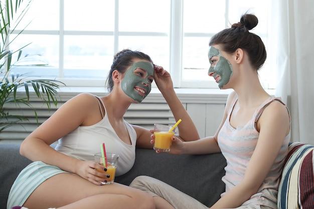 Donna che applica una maschera facciale al suo amico, concetto di cura di pelle