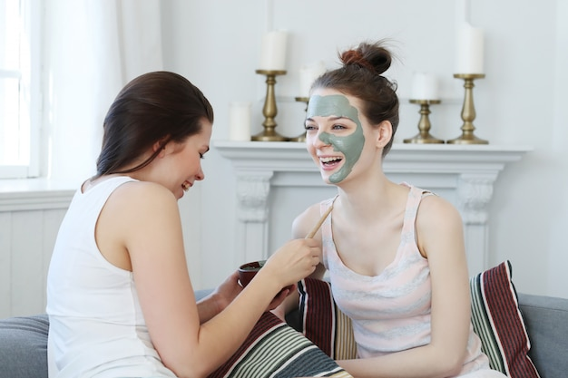 Woman applying a facial mask to her friend
