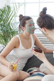 Donna che applica una maschera facciale alla sua amica