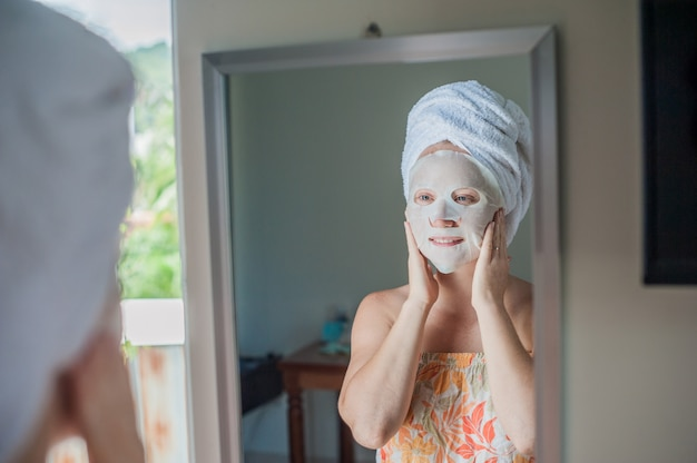 Woman applying a facial mask sheet