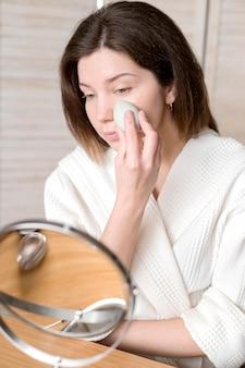 Женщина, применяя тональный крем с губкой