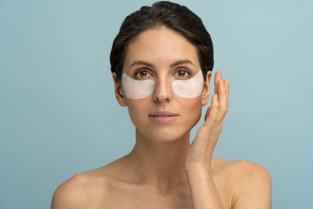 Женщина прикладывая изолированные патчи восстановления под глазами гидрогеля. красота ухода за кожей лица.