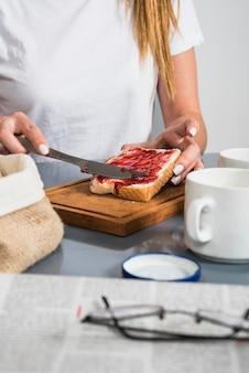 아침 식사 테이블에서 빵 조각에 잼을 적용하는 여자